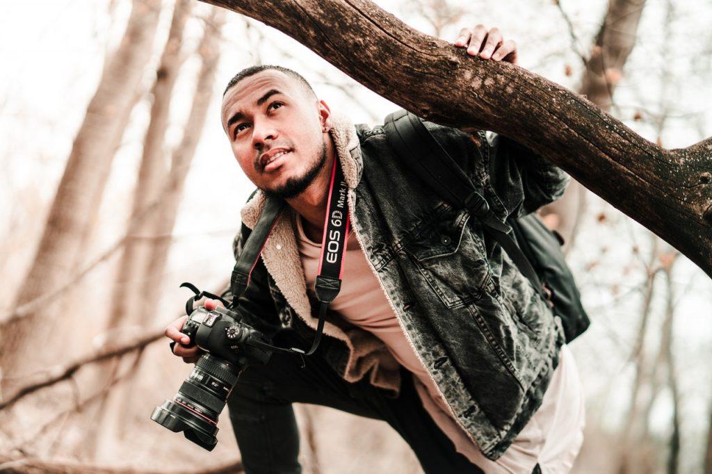 photographer holding tree branch