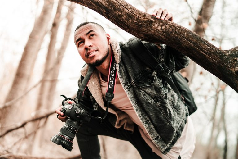photographer holding tree branch